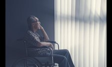 An elderly man in a wheelchair looks up at curtains covering a window